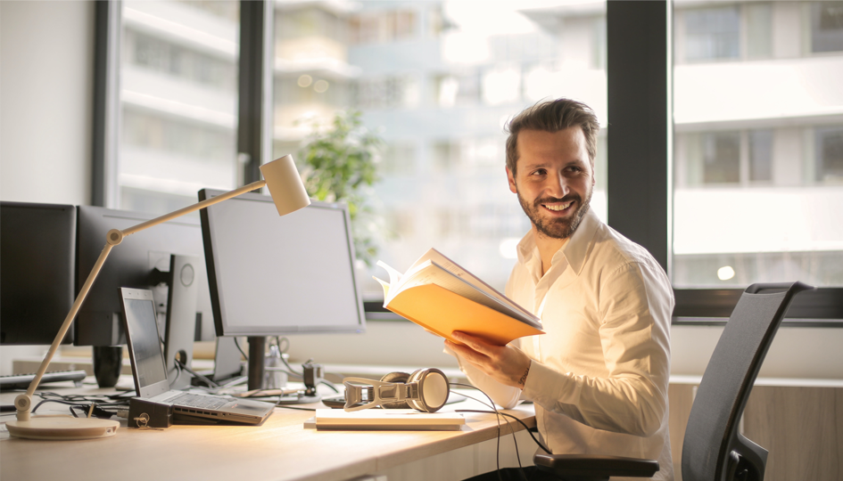 Smiling man at computer desk | Employee Assistance Plan | Benefits by Design