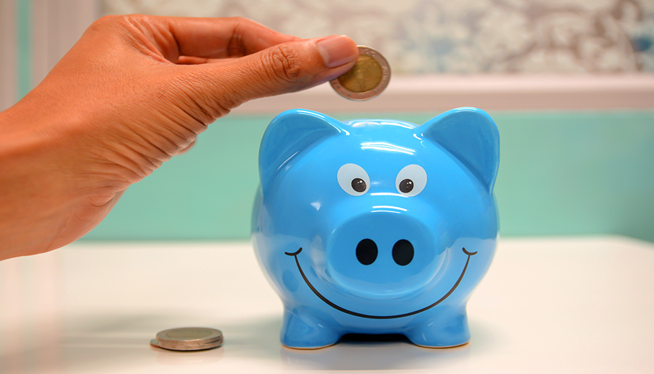 Blue Piggy Bank with a hand placing coins in | Spending Account | Benefits by Design