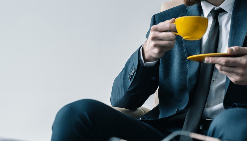Man in a suit drinking a cup of coffee from a yellow mug.