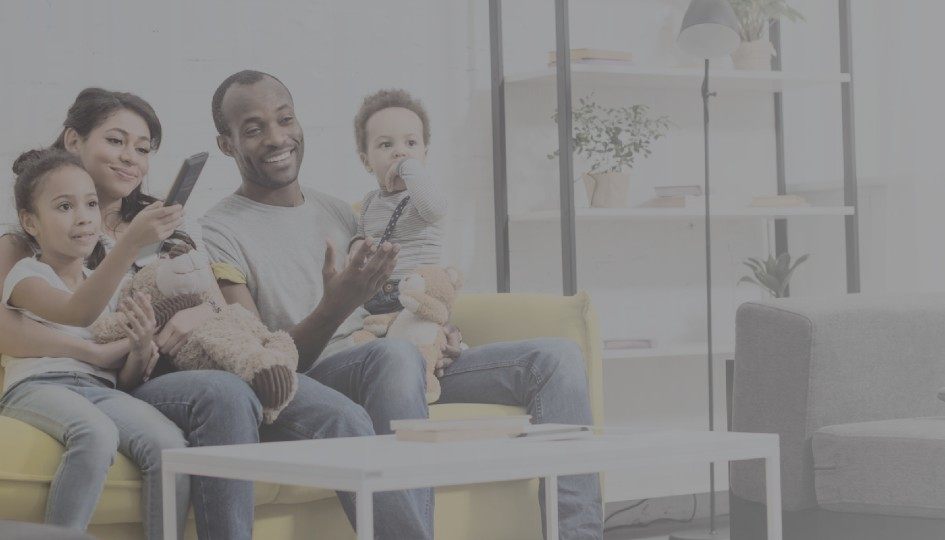 Family looking at a cellphone while sitting on a couch.