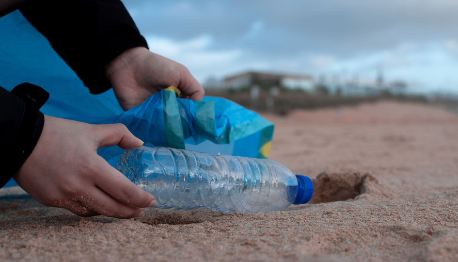 Plastic bottle on sand beach   Volunteering   Benefits by Design