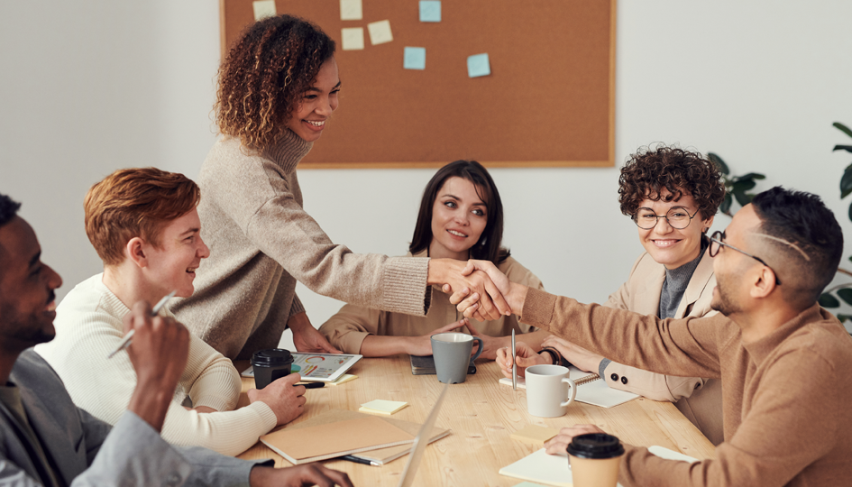 Happy employees shaking hands | Fully-Insured | Benefits by Design