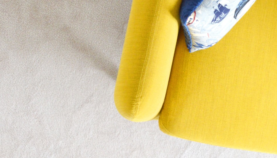 Yellow chair with a pillow on it