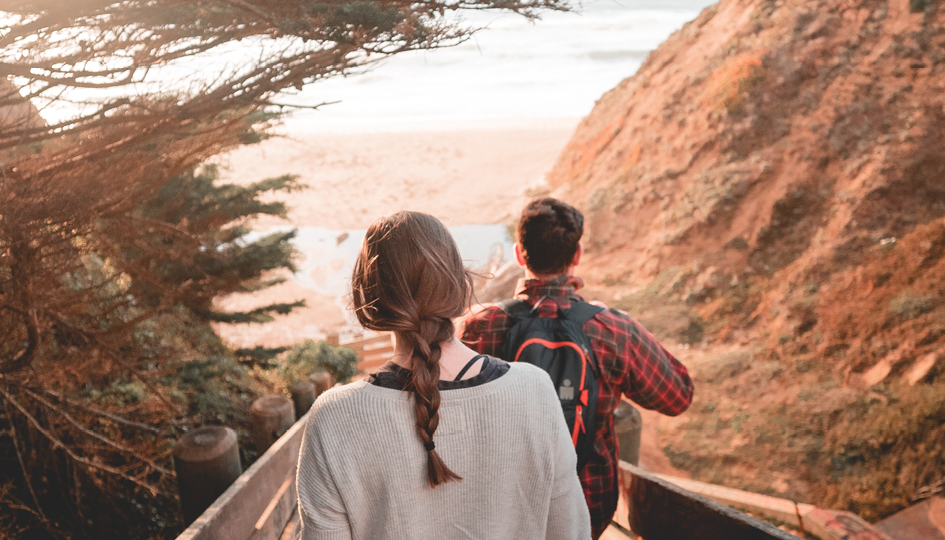 Two people walking on a beach | Vacation | Benefits by Design