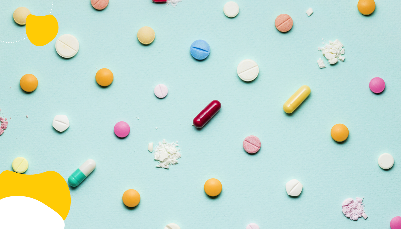Scattered pills on a teal background | Health Insurance | Benefits by Design